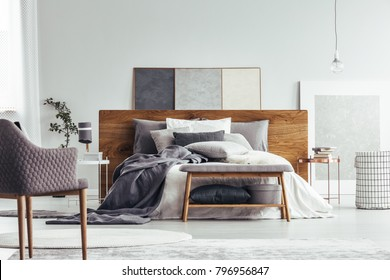 Wooden bench and armchair in cozy bedroom interior with copper table near bed and bag