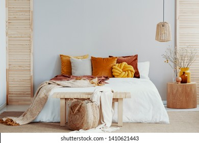 Wooden bench before king size bed with pillows and blanket, copy space on empty wall