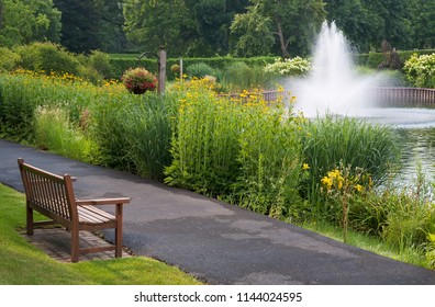 A wooden bench beside a paved walking path overlooks summer flowers and a pond with a fountain; Cantigny Park, DuPage County, Illinois