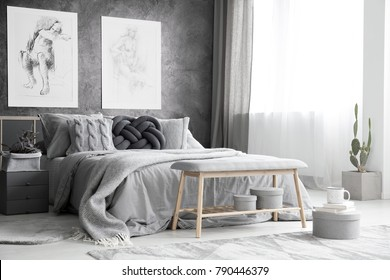 Wooden bench and boxes in monochromatic bedroom interior with drawings on concrete wall above bed