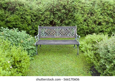 Wooden bench with bronze armrests in the garden.