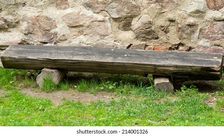 A wooden bench by the stone wall