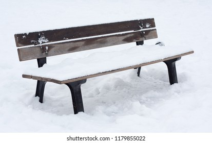 Wooden bench covered in snow in snow-covered park.