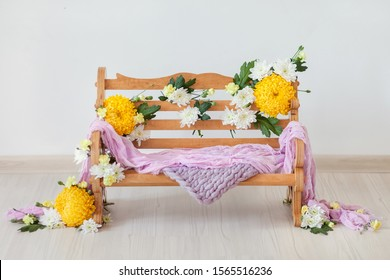 a wooden bench decorated with yellow and white chrysanthemums flowers on a light background with the addition of lilac fabric props for shooting newborns and children up to a year, the idea for a phot
