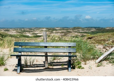 Wooden bench in the Dunes of North-Holland at a sunny day with a blue sky.