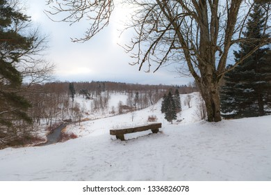 A wooden bench at the edge of a hill covered by the snow. Toila park, Estonia.