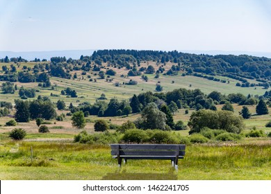 A Wooden bench in front of a Bavaria landscape .Bavaria, officially the Free State of Bavaria, is a landlocked federal state of Germany, occupying its southeastern corner.