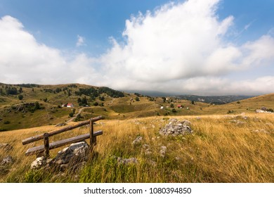 Wooden bench in front of lovely rural landscape with little villages in Durmitor National Park near Zabljak, Dinaric Alps, Montenegro