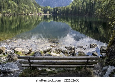 Wooden bench in front of a mountain lake reflecting the forrest and blue sky.
