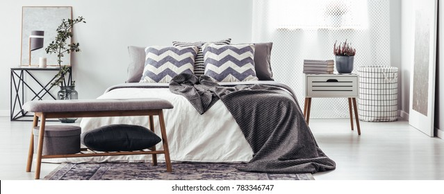 Wooden bench in grey bedroom interior with patterned pillows on bed and plant on white nightstand