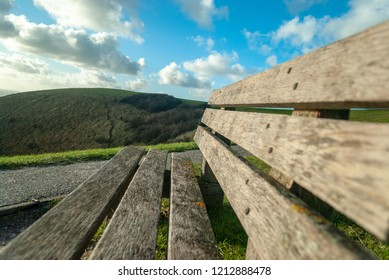 Wooden bench leading to rolling hills