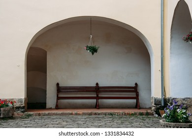 Wooden bench near the bricks wall with arched niche at castle