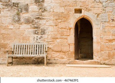 wooden bench near a medieval wall