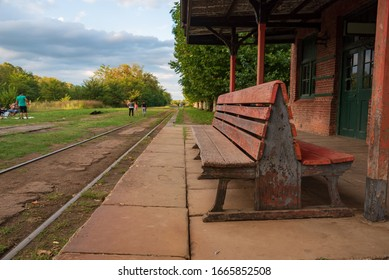 A wooden bench in an old abandoned train station with a view of the railroad with grass around it