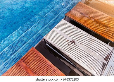 wooden bench on wooden deck nearby swimming pool