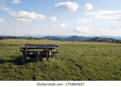 a wooden bench on a top of mountain with nice view to another hills
