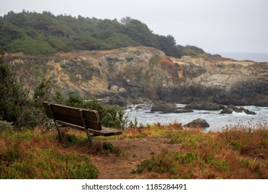 Wooden bench overlooking rocky cliffs on typical foggy day on Northern California coast