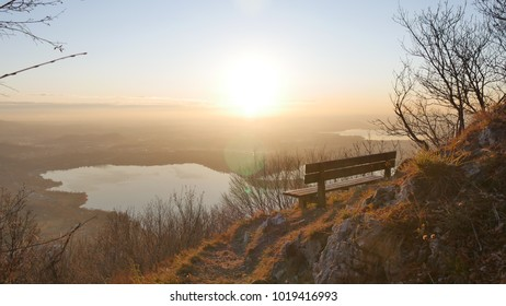 a wooden bench and the panorama of lake Pusiano, a beautiful mere close to lake Como, Lombardy, Italy and of the Po valley at sunset.