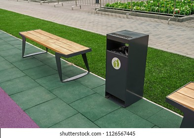 A wooden bench for rest and a garbage bin for waste in a city park