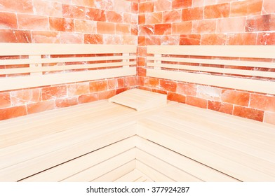 Wooden bench, salt wall and headrest support in sauna room as relaxation concept