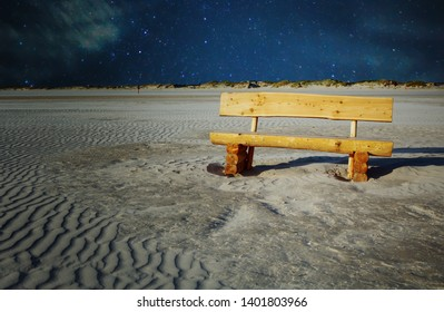 wooden bench in the sand by the beach in the night