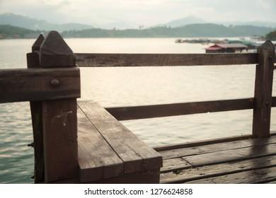 Wooden Bench Seat with beautiful natural morning sunrise over Songkalia river background on Saphan Mon Wooden Bridge (Mon Bridge), Thailand longest wooden bridge, Sangkhlaburi, Kanchanaburi, Thailand.