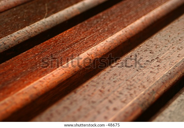 Wooden bench slats covered in raindrops.