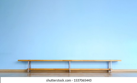 wooden bench stands on parquet floor in empty room with blue concrete wall