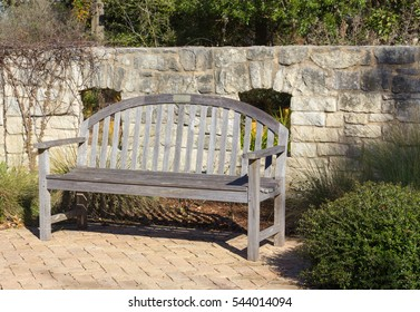 wooden bench stone wall and patio