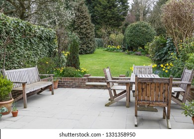 Wooden bench, table and chairs on a patio in a London suburban garden