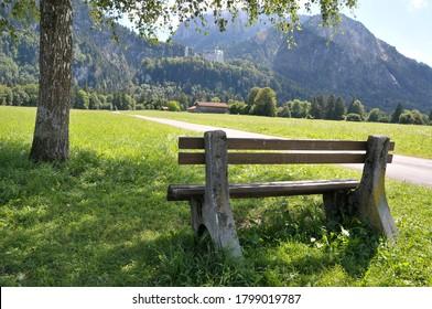 Banco de madera bajo un árbol en medio de un paisaje alrededor de Fussen
