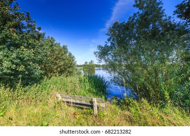 Wooden bench with a water view in nature reserve Willeskop at the town of Oudewater
