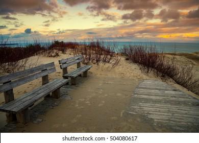 Wooden benches in embankment. Sunset over Parnidis dune in autumn, Neringa, Lithuania