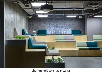 Wooden benches with multi-colored seats. Seats are made up of pillows. At the back on bench there is a digital clock which made from the transparent rectangles. Left wall is from concrete and back