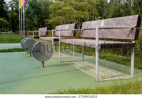 Wooden benches in the park. City Garden. A place to relax. Relax surrounded by greenery. Relaxing in the fresh air. Walk in the park. Spring in the city. Healthy lifestyle.