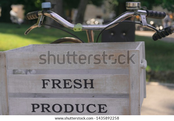 Wooden bike basket on fresh bio produce vegetables attached in front of bicycle handlebar. Traditional ecological bicycle delivery service with old empty vintage crate box in Bergamo, Italy.