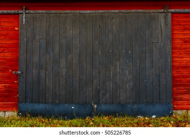 Wooden black sliding door on red barn.