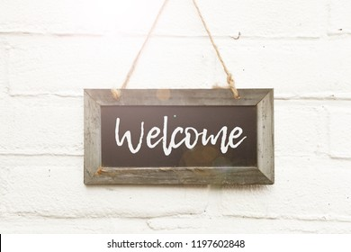 Wooden blackboard with text hello welcome home sign board against white brick wall in sunlight