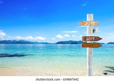 wooden blank sign with text 2018 and 2017, Over Blurred blue sea and sand beach with cloudy blue sky , Image for New year 2018 Concept.