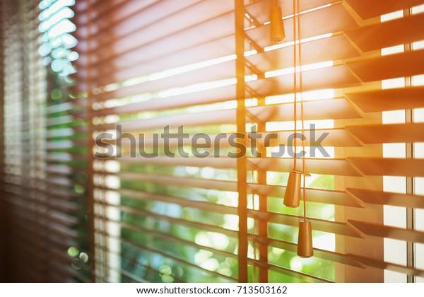 Houten jaloezieën met zonnestralen.
