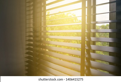 Wooden blinds with sunlight in dark room
