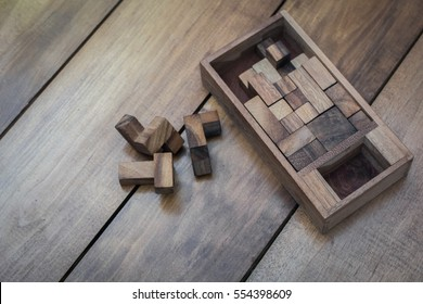 Wooden Block Brain Teaser Puzzle on Wood Background Top View