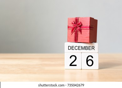 Wooden block calendar 26 December and red color gift box on wood table with white wall background, Happy boxing day sale concept, Copy space your text