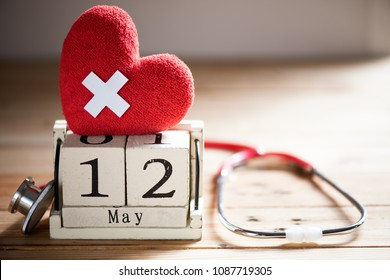 Wooden Block calendar for International Nurses Day, May 12. Healthcare and medical concept. Red heart with Stethoscope on wooden table background.
