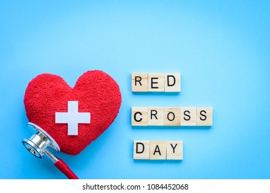 Wooden Block calendar for World Red Cross and Red Crescent day, May 8. Healthcare and medical concept. Red heart with Stethoscope on blue background.