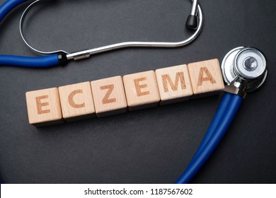 Wooden block form the word ECZEMA  with stethoscope. Medical concept.
