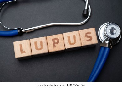 Wooden block form the word LUPUS with stethoscope. Medical concept.