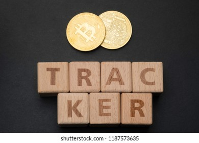 Wooden block form the word TRACKER with bitcoins. Cryptocurrencies concept.
