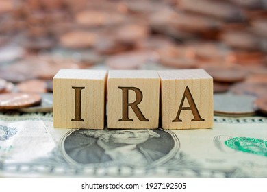 Wooden block with the letter IRA with some money around. Concept: Retirement Plan in USA, Individual Retirement Account