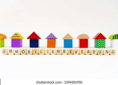 """Wooden block with letters saying """"Immobilienbewertung"""" (German for real estate rating) in front of colorful toy houses"""